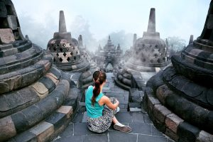 Girl sitting on the top of Borobudur temple. Indonesia